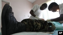 In this Oct. 28, 2010 photo, a doctor and a nurse perform a circumcision procedure on a Zimbabwean soldier at a local clinic in Harare, Zimbabwe. The U.S. Agency for International Development is leading a war on AIDS that may help save hundreds of thousan