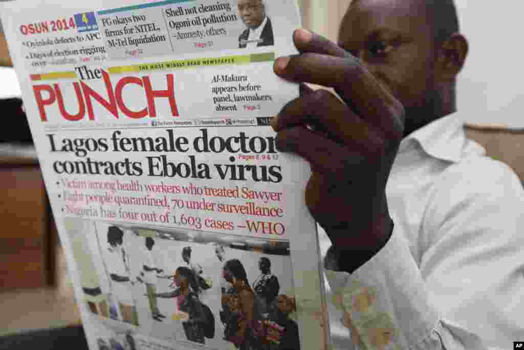 A man reads a local newspaper with headline news about a Lagos female doctor who contracted Ebola, in Lagos, Nigeria, Aug. 5, 2014.