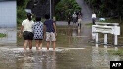 Trẻ em đi bộ qua một con đường bị ngập sau trận bão Roke ở Toyota, miền trung Nhật Bản, ngày 21/9/2011