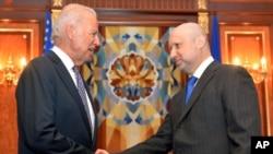 El vicepresidente Joseph Biden estrecha la mano del primer ministro en funciones de Ucrania, Oleksandr Turchynov.