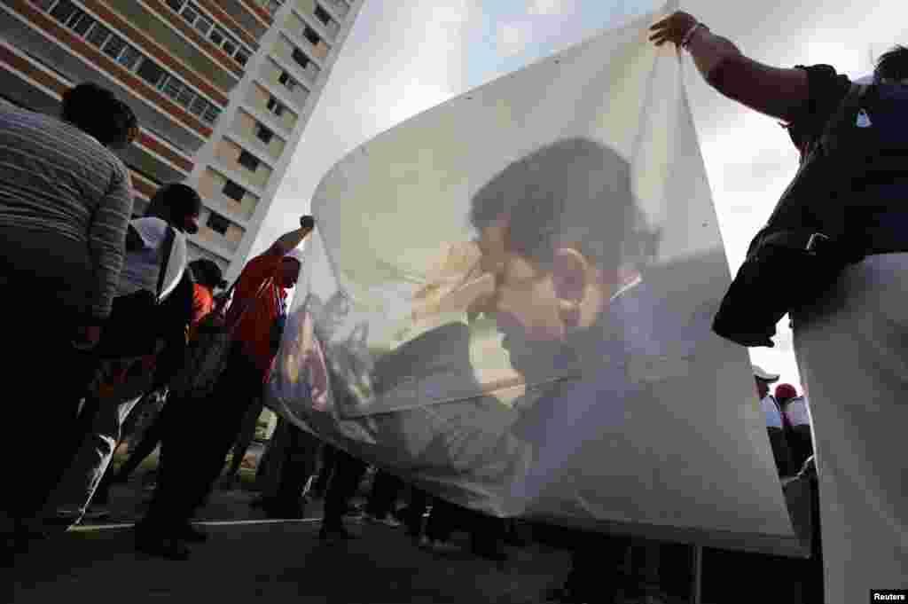 Sinh viên Venezuela tụ tập ở thủ đô La Habana của Cuba trương ảnh của Tổng thống Hugo Chavez để tỏ lòng ủng hộ. Chính phủ Venezuela tỏ vẻ lạc quan về tình hình trị ung thư của ông Chavez tại Cuba, nhưng ông đã không xuất hiện trước công chúng từ 8 tuần qua.