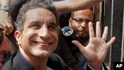 Bassem Youssef, Egyptian TV satirist, waves to supporters in Cairo before talks with authorities about charges he insulted Islam and the nation's president, March 31, 2013.