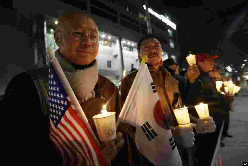 South Korean conservative activists hold candles during a rally to wish U.S. Ambassador to South Korea Mark Lippert a quick recovery, in front of Severance Hospital where he is hospitalized, in Seoul.  Police on Friday investigated the reason why the anti-U.S. activist they say slashed Lippert.