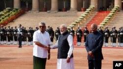 PM India Narendra Modi (tengah), berjabat tangan dengan presiden Sri Lanka, Gotabaya Rajapaksa, disaksikan Presiden India Ram Nath Kovind di New Delhi, 29 November 2019.