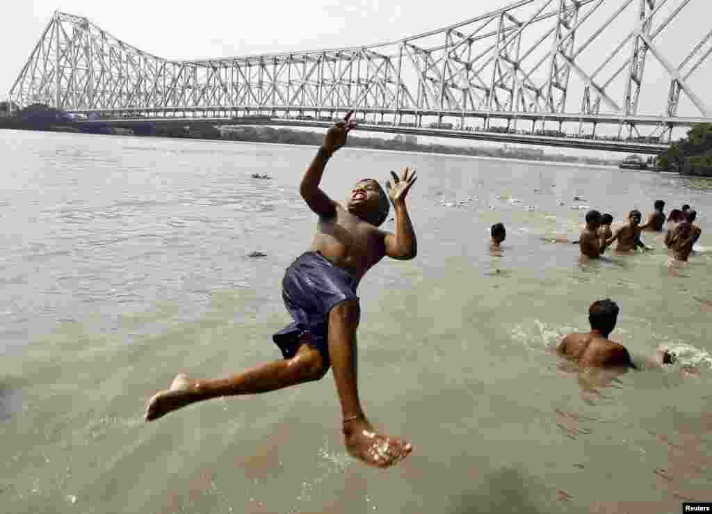 Seorang pria terjun ke sungai Gangga di hari yang panas di Kalkuta, India. Suhu di Kalkuta diperkirakan mencapai 37 derajat Celsius.