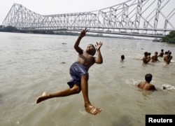 A boy jumps into the Ganges river to cool off himself on a hot summer day in Kolkata, India, May 6, 2015. Temperature in Kolkata on Wednesday is expected to reach 37 degree Celsius (98.6 degree Fahrenheit).