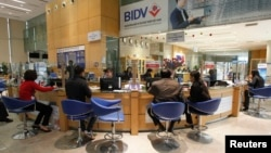 FILE - Clients sit in a branch of the Bank for Investment and Development of Vietnam (BIDV), Hanoi.