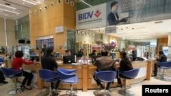 Khách hàng ngồi tại một chi nhánh của Ngân hàng Đầu tư và Phát triển Việt Nam (BIDV) tại Hà Nội.