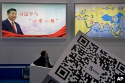"An attendee at a conference looks up near a portrait of Chinese President Xi Jinping with the words ""Xi Jinping and One Belt One Road"" and ""One Belt One Road strategy,"" in Beijing, April 28, 2017. The ""Belt and Road Forum"" opens Sunday."