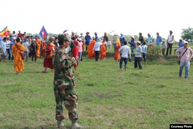 Nhiều người Việt đội mũ bảo hiểm, cầm gậy gộc và súng đứng đối diện với sư sãi và người Campuchia cầm quốc kỳ.
