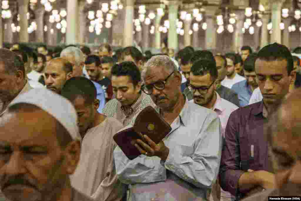 A muslim man attends the prayers while he follows the Imam reading in his Quran in Amru Ebn Alaas mosque in old Cairo, Egypt, June 21, 2017. (Hamada Elrasam/VOA)