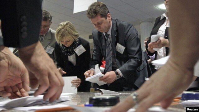 Members of the local electoral commission count ballots at a polling station after the parliamentary election in Minsk, Belarus, September 23, 2012.