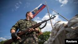 2014年6月24日一名亲俄分离分子在东乌卢甘茨克地区的里斯坦斯克镇外路上的检查哨警戒。