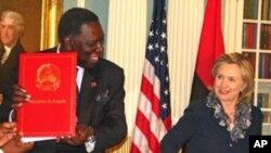 Razão para sorrir. Ministro dos Negócios Estrangeiros de Angola Assunção dos Anjos mostra o acordo assinado com Hillary Clinton