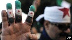 시리아 혁명깃발 모양으로 색칠한 손을 보이는 반정부 시위대. 아랍국가 외무장관 회담이 열리고 있는 카이로의 아랍연맹 본부 앞.