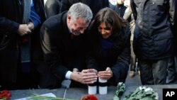 FILE - New York City Mayor Bill de Blasio and Paris Mayor Anne Hidalgo light candles in tribute to the victims of the terror attack against Charlie Hebdo at Place de la Republique in Paris, Jan. 20, 2015.