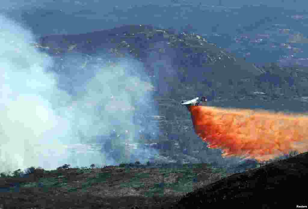 A water bomber makes a drop on the Coco Fire as fire fighters continue their battle in the hills surrounding San Marcos California. Wildfires were raging in southern California, keeping thousands of residents and students away from their homes after San Diego county officials maintained evacuation advisories.