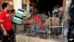 Pemilik toko Irak memeriksa kerusakan di tokonya pasca ledakan bom mobil di wilayah Kut, 160 kilometer sebelah tenggara kota Baghdad, Irak (16/6).