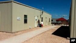 Dua orang tampak memasuki pusat penanganan imigran tak berdukumen, khususnya untuk para ibu dan anak, di Artesia, New Mexico, 10/9/2014.