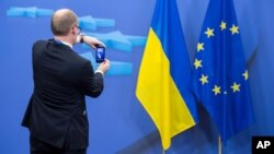 A member of a delegation takes a photo with his cellphone of the Ukrainian and EU flags after an EU summit in Brussels, March 6, 2014.