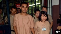 Thai student Patiwat Saraiyaem, 23, left, and activist Porntip Mankong, 26, are escorted by prison security guards after their verdict at the Criminal Court in Bangkok, Feb. 23, 2015.