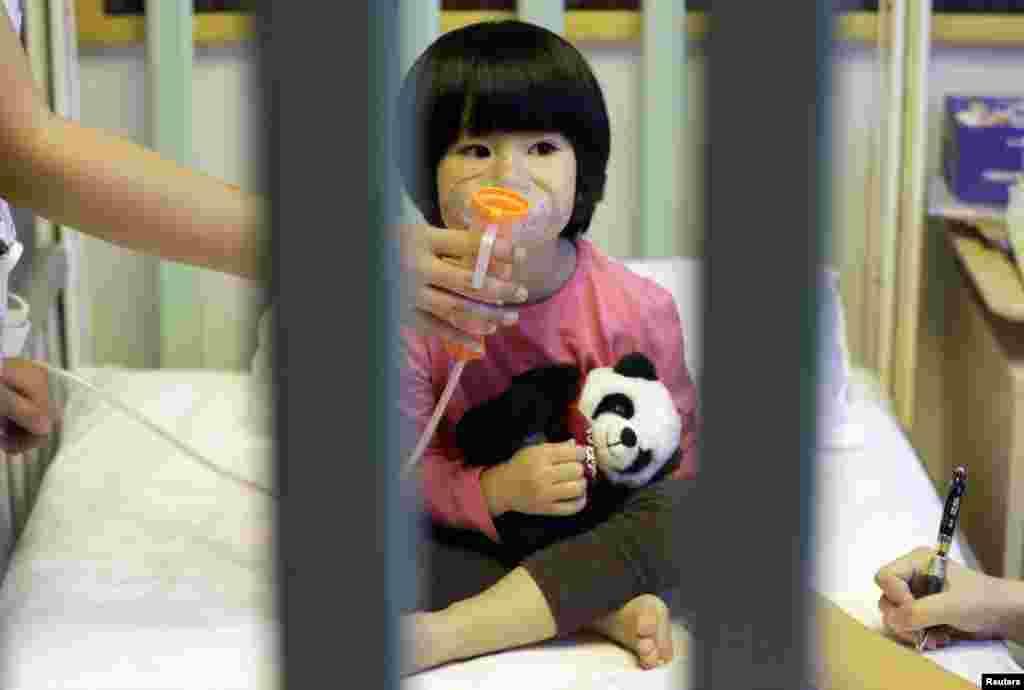 중국 베이징에서 심각한 대기오염으로 올해들어 두 번째 적색경보가 발령된 가운데, 2살 펭펭 양이 '신세기국제어린이병원'에서 의료용 분무기 치료를 받고 있다.