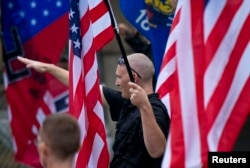 "FILE - A member of a white supremacy group gives a fascist salute during a gathering in West Allis, Wisconsin, Sept. 3, 2011. ""The number of hate groups in the United States rose for a second year in a row in 2016 as the radical right was energized by the candidacy of Donald Trump,"" according to the Southern Law Poverty Center, a U.S. rights group."