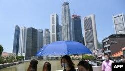 戴着口罩的人们走过新加坡金融区附近的一座桥。(2021年4月20日)