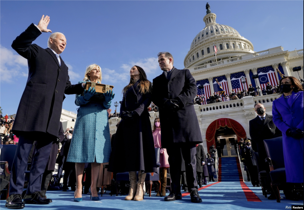 Joe Biden is sworn in as the 46th president of the United States by Chief Justice John Roberts as Jill Biden holds the Bible during the 59th Presidential Inauguration at the U.S. Capitol.