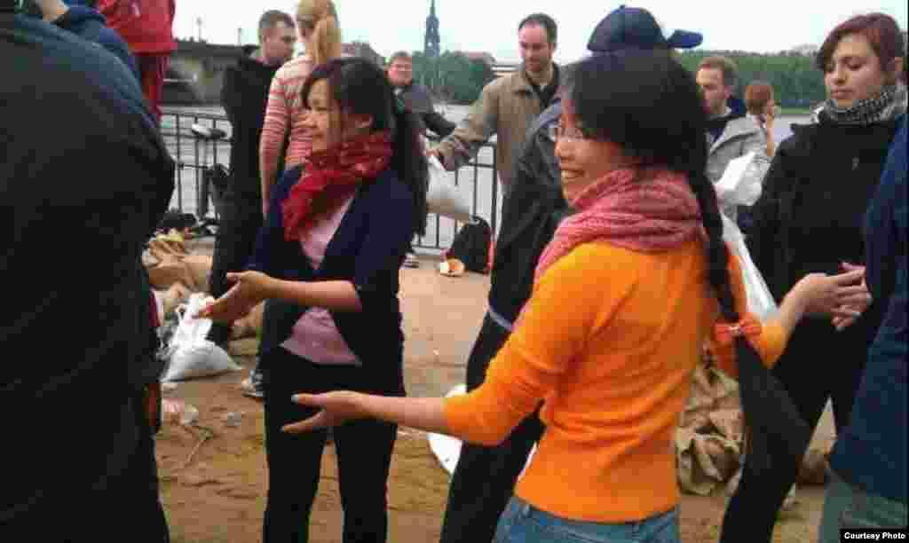 Người Việt ở Dresden cũng chung tay giúp chuyền bao cát chống lũ. (Ảnh: Bùi Trương Bình)