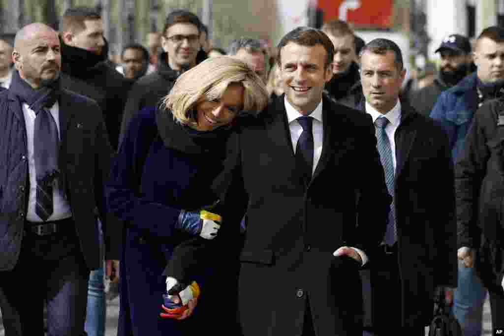 French President Emmanuel Macron and his wife Brigitte Macron walk down the Champs-Elysees avenue after the opening of the Cafe Joyeux coffee shop, in Paris. This chain of coffee shops is operated by people with Down syndrome, autism and other disabilities.
