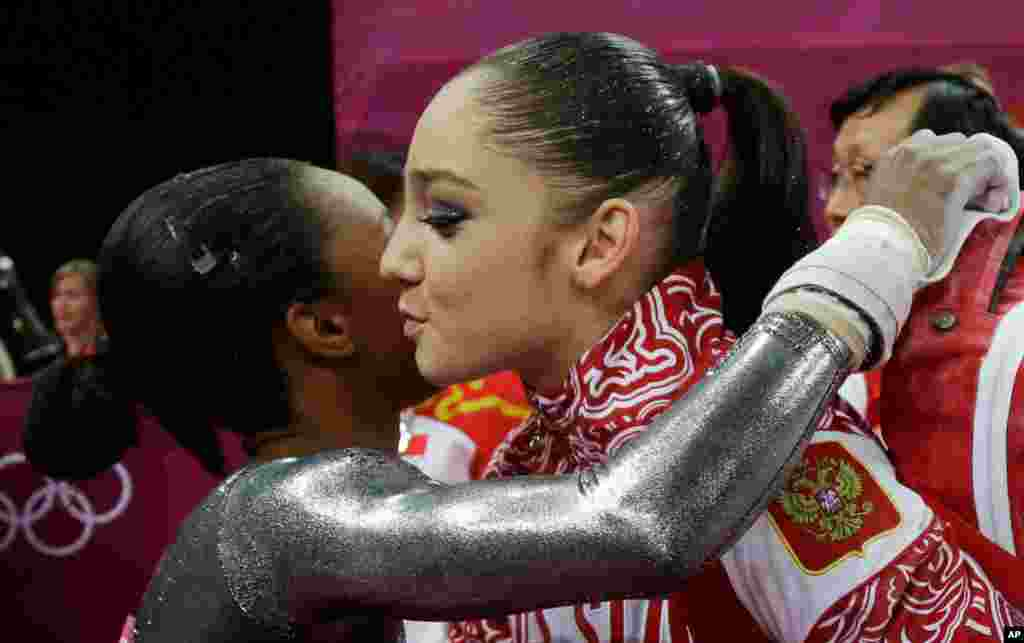 U.S. gymnast Gabrielle Douglas, left, congratulates Russia's Aliya Mustafina for winning the gold for the uneven bars during the artistic gymnastics women's apparatus finals.