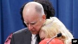 """Gubernur California Jerry Brown (kiri) dipeluk oleh Holly Dias, seorang pekerja di restoran waralaba """"Burger King"""" yang memuji keputusan upah minimum $15/jam di sana (foto: dok)."""