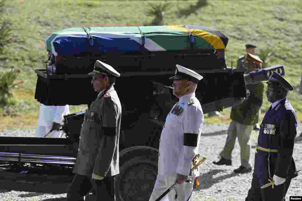 The coffin of South African former president Nelson Mandela is carried on a gun carriage for a traditional burial after the funeral ceremony in Qunu, South Africa, Dec. 15, 2013.