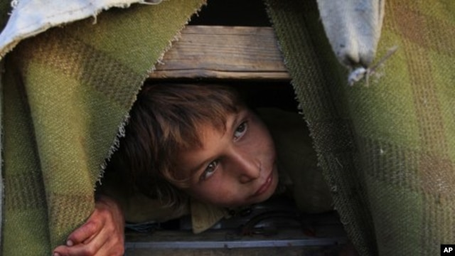 An Afghan refugee boy, Gul Zaman, who fled from Afghanistan with his family, peeps from his make-shift tent in the outskirts of Karachi, Pakistan, March 13, 2012.
