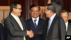 Cambodian Prime Minister Hun Sen, second from right, shakes hands with the main opposition party leader Sam Rainsy, left, of Cambodia National Rescue Party, as Deputy Prime Minister Sar Kheng, second from left, looks on after a meeting in Senate headquarters, Phnom Penh, Cambodia, July 22, 2017)