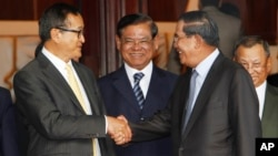 Cambodian Prime Minister Hun Sen, second from right, shakes hands with the main opposition party leader Sam Rainsy, left, of Cambodia National Rescue Party, as Deputy Prime Minister Sar Kheng, second from left, looks on after a meeting in Senate headquarter, Phnom Penh, Cambodia.