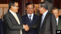 Cambodian Prime Minister Hun Sen, second from right, shakes hands with the main opposition party leader Sam Rainsy, left, of Cambodia National Rescue Party, as Deputy Prime Minister Sar Kheng, second from left, looks on after a meeting in Senate headquart