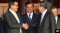 Cambodian Prime Minister Hun Sen, second from right, shakes hands with the main opposition party leader Sam Rainsy, left, of Cambodia National Rescue Party, as Deputy Prime Minister Sar Kheng, second from left, looks on after a meeting in Senate headquarter, file photo.