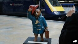 Tourists take photographs on their tablets and smart phone of a statue of 'Paddington Bear' on the platform at Paddington railway station in London.