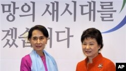 Pemimpin oposisi Burma, Aung San Suu Kyi (kiri) berjabat tangan dengan Presiden terpilih Korea Selatan, Park Geun-hye di Seoul, Korea Selatan, 29 Januari 2013 (AP Photo/Jung Yeon-je, pool).