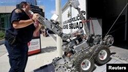 Tehničar policijskog odreda za demontiranje bombi iz Klivelnda utovaruje robotsko vozilo tipa Remotec F5A posle demonstracije policijskim mogućnosti u blizini mesta, gde će sutra početi Republikanska nacionalna konvencija