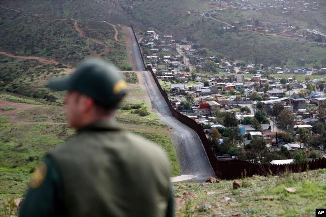 Agent Granične patrole posmatra granični zid koji odvaja gradove Tijuana u Meksiku i San Diego u SAD, 5. februara 2019.