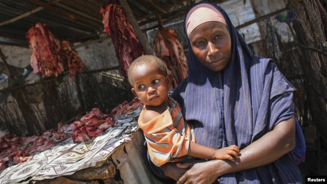 A Somali woman selling meat from a kiosk holds her child in a market area in the centre of the southern Somali port city of Kismayo, October 7, 2012.