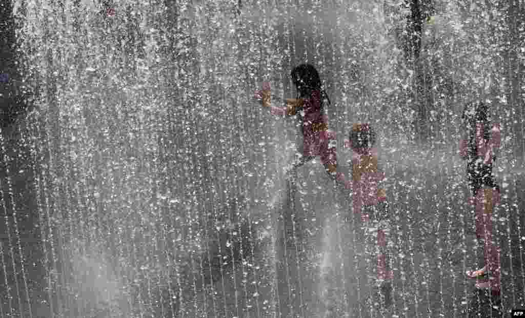 Children play in a water fountain in central London.