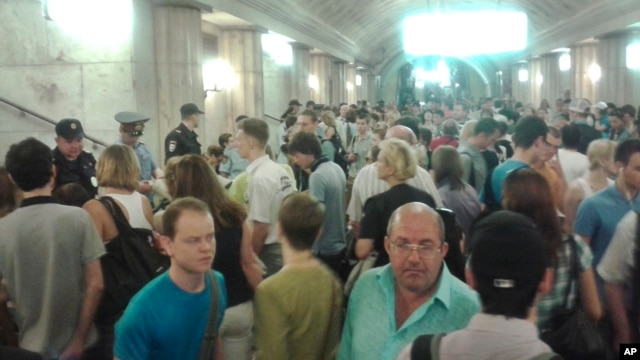 In this image made with a mobile phone camera, people leave a subway station in Moscow Wednesday, June 5, 2013. A rush-hour fire in Moscow's subway injured dozens of people, forced the evacuation of thousands of commuters.