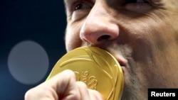 迈克尔·菲尔普斯亲吻他的金牌(2016年8月9日)。