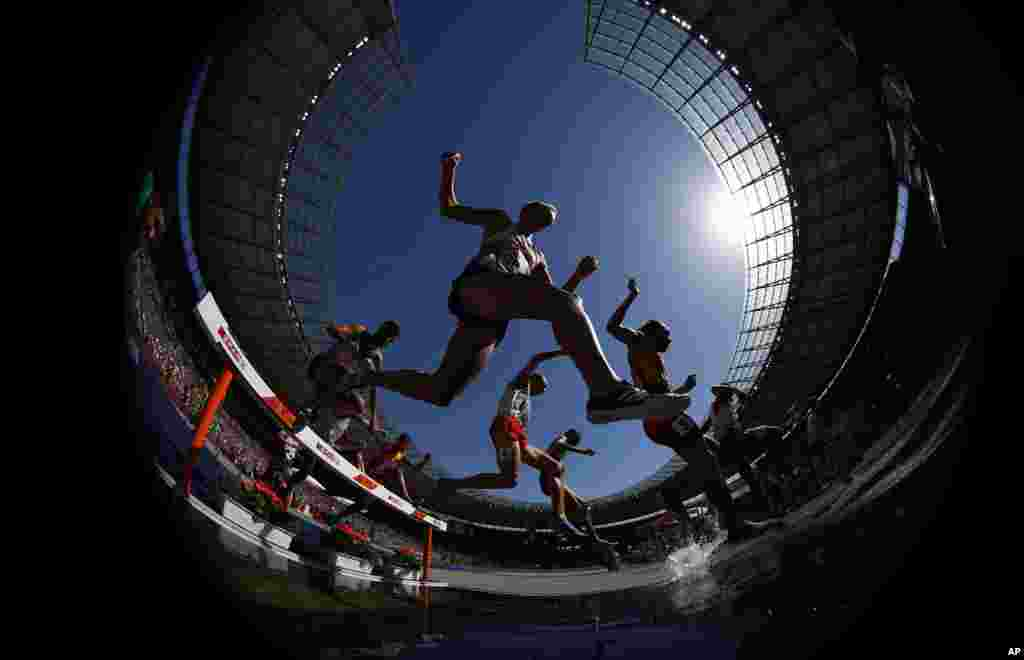Athletes clear the water in a men's 3000-meter steeplechase heat at the European Athletics Championships at the Olympic stadium in Berlin, Germany.