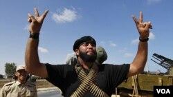 Seorang pejuang pemberontak Libya mengisyaratkan simbol kemenangan saat bersiap menyerang daerah pertahanan Gaddafi di Sirte (24/9).