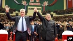 En esta fotografía del domingo 4 de noviembre de 2018 publicada por el gobierno norcoreano, el presidente cubano Miguel Díaz-Canel, izquierda, y el líder norcoreano Kim Jong Un elevan sus manos unidas durante una ceremonia de bienvenida al gobernante caribeño, en Pyongyang, Corea del Norte.